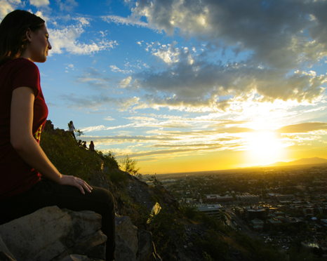 woman on mountain looking at sunset