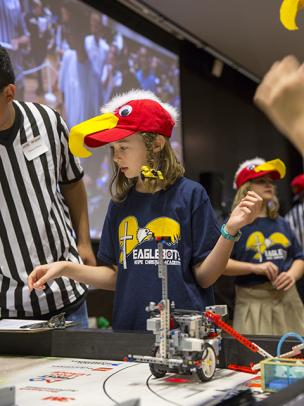 Donned in colorful eagle hats, members of the Eaglebots team, from Hope Christian Academy in Chandler, Arizona, prep their robot's first run at the FIRST® LEGO League state championship tournament on January 15, 2017.