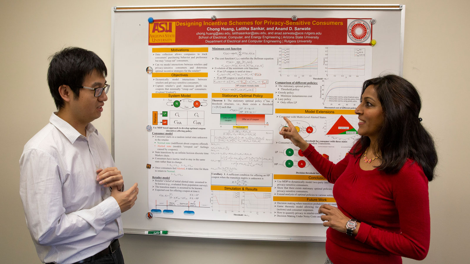 Lalitha Sankar and Chong Huang talk in front of a research poster.