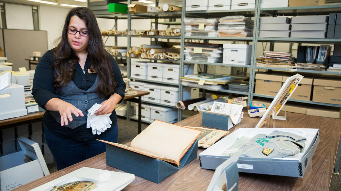 A woman display archival items on a table
