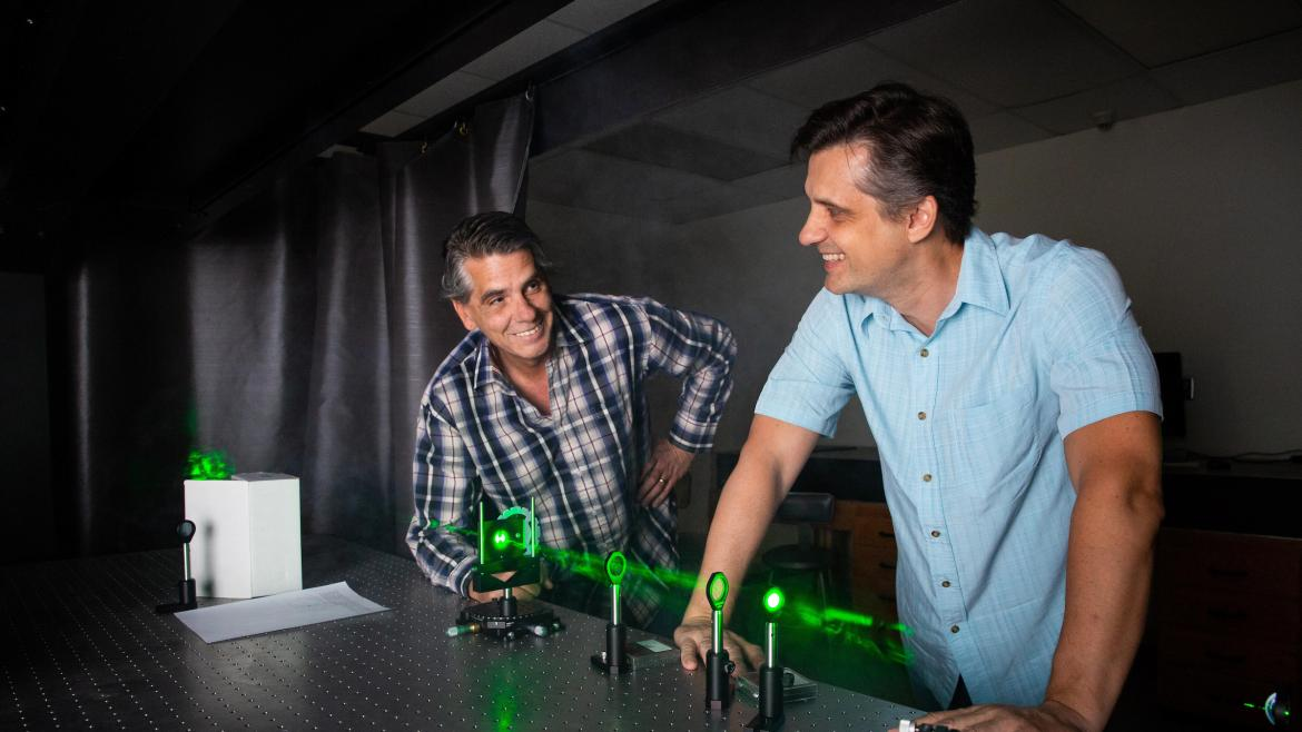 two men working on lasers in lab