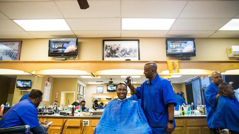 Men have their hair cut in a barbershop.