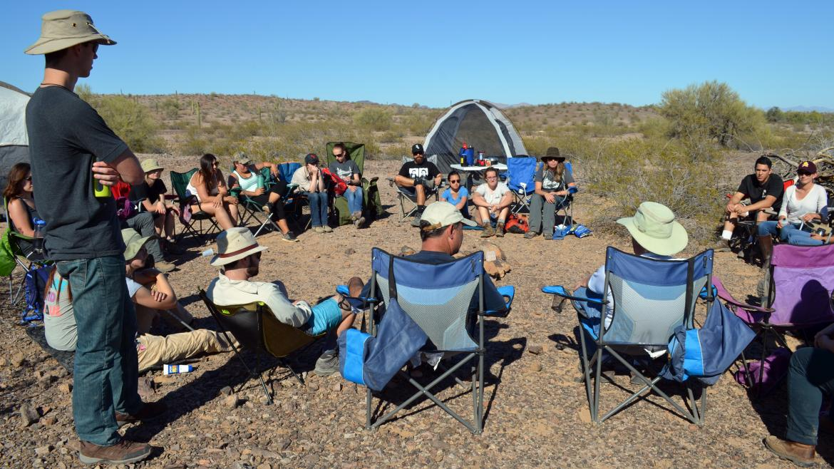 Students sit in a circle in the desert on a biology camping trip.