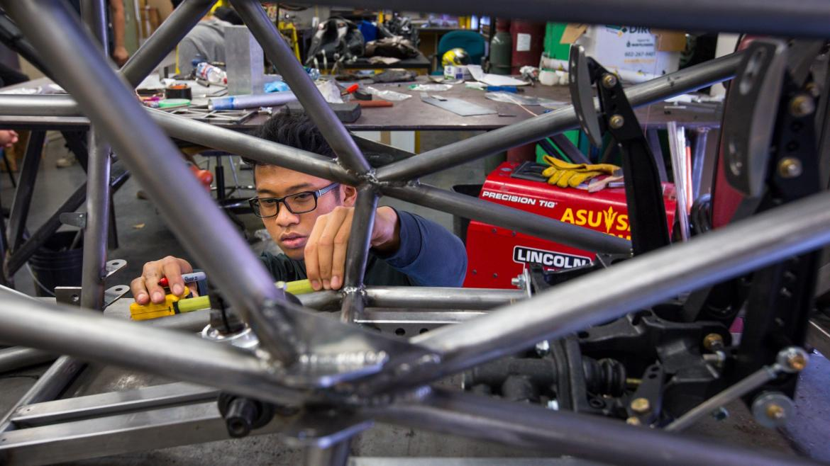 A student engineer works on the chassis of a race car.