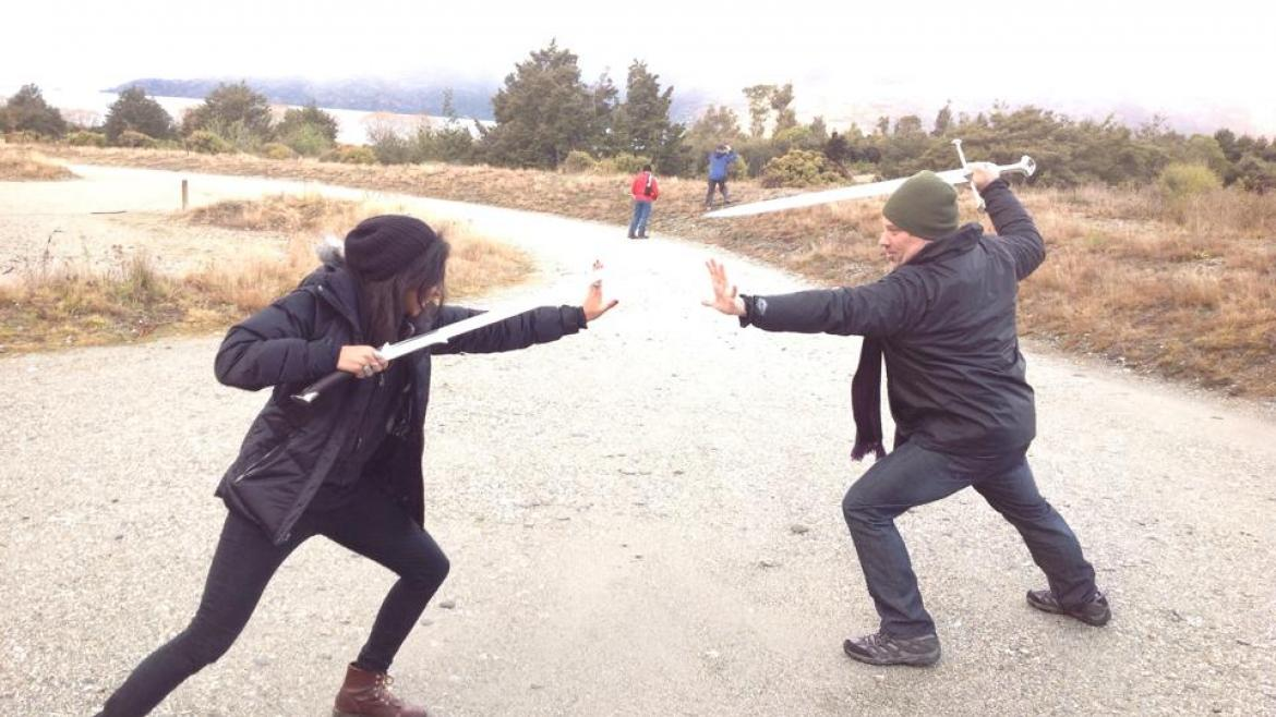 Two people play-fight with Tolkien-inspired swords.