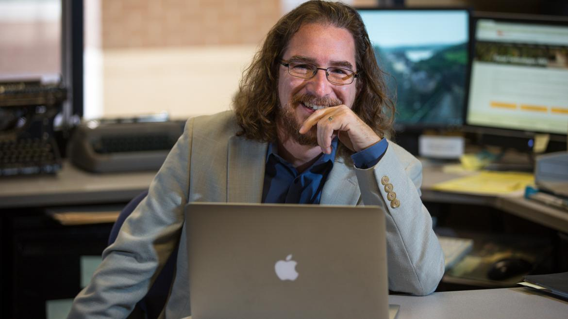 ASU professor Greg Wise sits at a laptop in his office