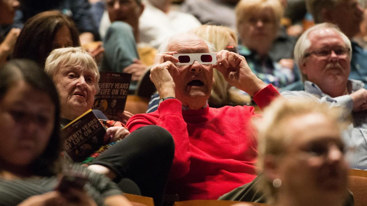 A man in a theater audience wears 3-D glasses.