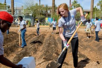 female student digging at a work site during the CGIU day of service
