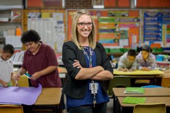 Lauren Edgar posing in a grade school classroom