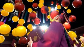 graduate looking at graduation balloons launched during convocation