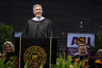 Arne Duncan speaking at podium during ASU undergraduate commencement