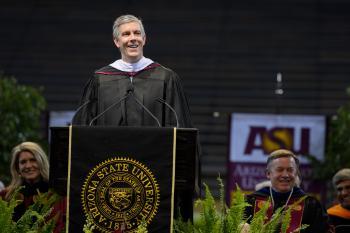 Arne Duncan speaking at podium during ASU undergraduate commencement