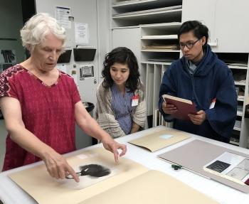 ASU-LACMA Fellows Ariana Enriquez and Matthew Villar Miranda work with Janice Schopfer, senior paper conservator in LACMA's Conservation Lab.