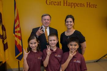 ASU President Michael Crow posing with parent and students of ASU Prep Academy