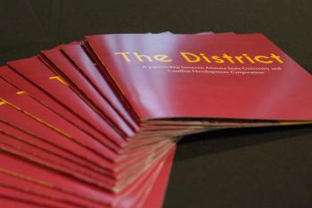 stack of The District booklets