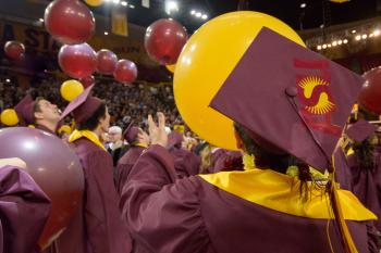 graduates in caps and gowns watching balloons drop at graduation