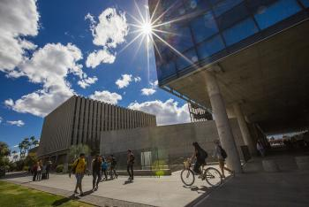 Students walking across campus in front of Coor Hall at ASU