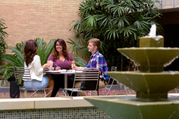 Three ASU students talking at a table outside on campus