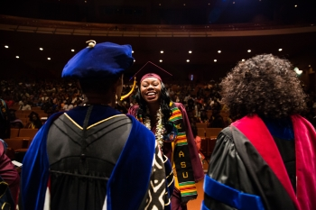 Graduates make their way through shaking hands of faculty during the Black and African Convocation at ASU Gammage on Thursday, May 12, 2016.