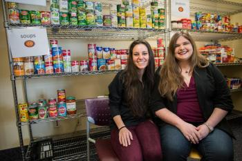 two women seated in front of shelves of canned food