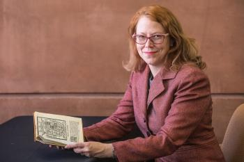 Curator sitting with 17th century text
