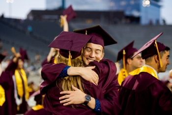 two grads giving each other a hug