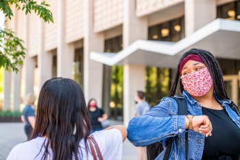Students wearing masks share an elbow bump while passing each other