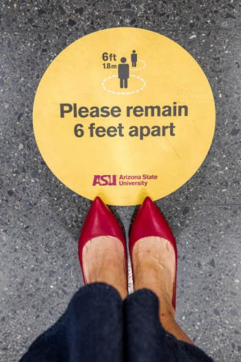 "A yellow sign on the ground that says ""Please remain 6 feet apart."""