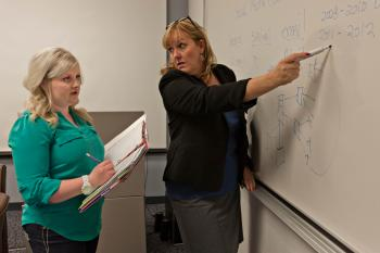 student and professor looking at white board