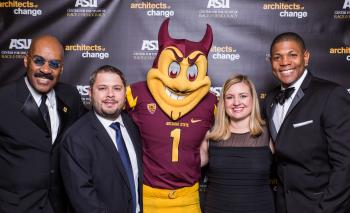 group of people pose with Sparky the Sun Devil at a gala event