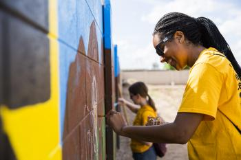 Students paint a mural during the Devils in Disguise day of service.