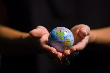 Hands hold a tiny globe