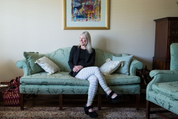 ASU Professor Devoney Looser is pictured seated on a sofa in her living room in her house.