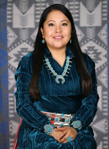 Jennifer Harrison (medium complexion with long dark hair, wearing native american turquoise jewelry and a dark teal dress) sits before a gray and white woven Native American tapestry