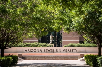 A statue stands above an ASU sign framed by green trees