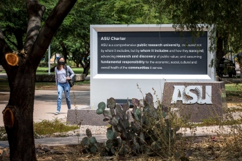 A student walks past the ASU charter sign