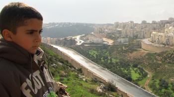 Palestinian filmmaker's son looks over at Israeli settlements from above