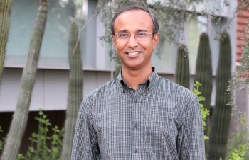 ASU researcher Rahman Masmudur smiling in front of some cacti, wearing glasses and a button down shirt