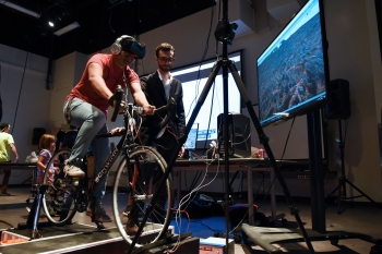 Kyle Hoefer presents his virtual reality biking system to another student at the digital culture showcase