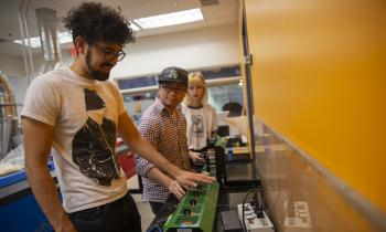 Three students work with the 3D printing plastic recycling tool.