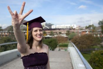 ASU grad standing on bridge