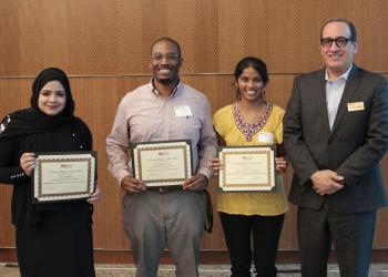 The three broadly smiling awardees show off their certificates alongside the Dean.