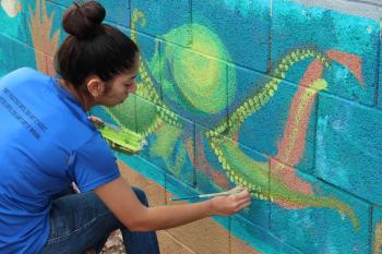 girl in blue shirt paints yellow octopus