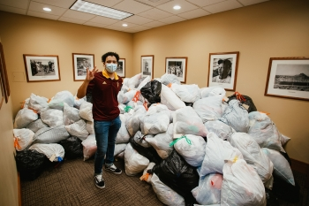 ASU student Ahlias Jones stands by nearly 2,000 pounds of clothing donated by students in the Medallion Scholarship Program