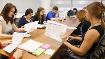 law students sitting at a conference table reading documents