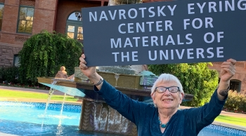 Professor Alexandra Navrotsky holds a sign for the opening of the Navrotsky Eyring Center for Materials of the Universe