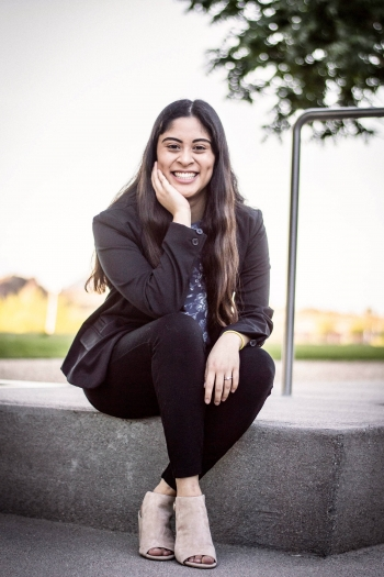Alexandra Kepler smiling and sitting outside on a concrete curb.