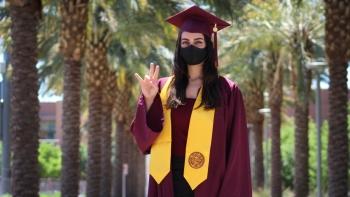 ASU graduate Almasi Sepideh wearing graduationg gown, robe, hat and face mask