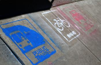 sidewalk painted with public transit signs