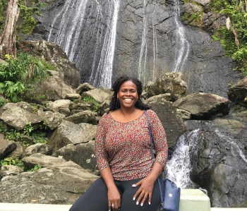 Anaís Deliah Roque smiles while sitting in front of a waterfall